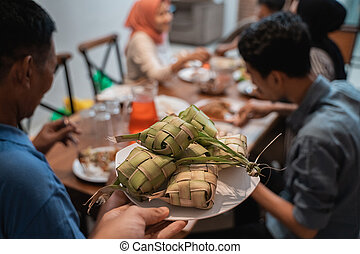 ketupat with people eating on the background - close up of...