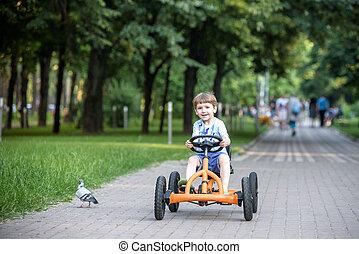 kevés, preschool, fiú, vezetés, nagy, játékszer, sportkocsi, és, having móka, outdoors.