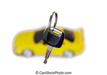 Key from the car close up and the yellow car in the background isolated on white
