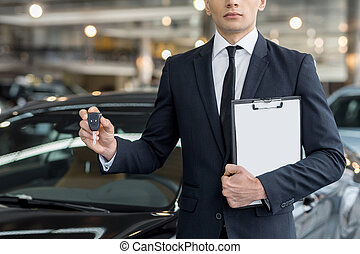 Key from your new car. Cropped image of young car salesman standing at the dealership and holding a key