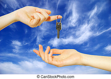 key in hands - Hands with key on a background sky...