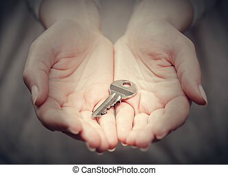 Key in womans hand in gesture of giving