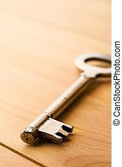 Key isolated on wooden background