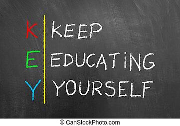 Key keep education yourself text on blackboard