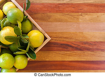 Key lime or Mexican lime in a wooden box on floor, one of main ingredient thai food and traditional pie. Stock photo