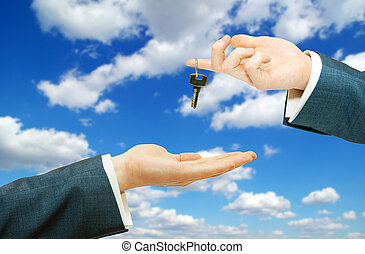 key - Hands with key on a background sky...