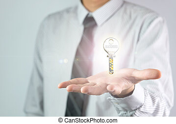 Key to success - Businessman holding a key with the word...