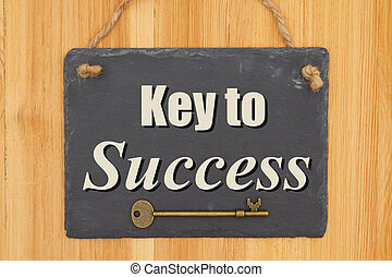 Key to success type message on a hanging chalkboard sign with skeleton key