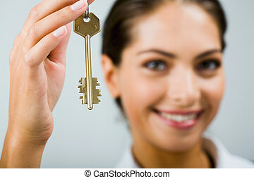 Key to the future - Smiling business woman is holding the...