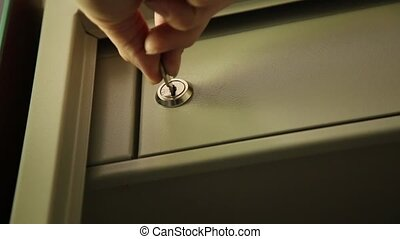 Key unlocked a safe latch and opening door safety deposit box. man folds documents and pc tablet