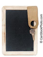 key with blank label on small school wooden blackboard