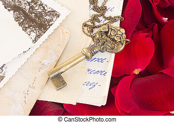 Key with old papers and rose petals