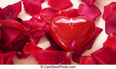 Burning candle heart with falling fresh red rose and petals