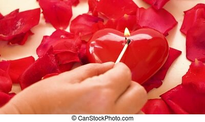 Someones hand fire a candle heart with fresh rose and petals on natural beige background
