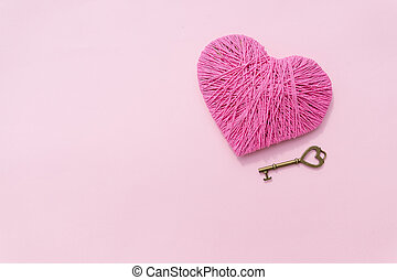 Key with the heart as a symbol of love, vintage card with heart on soft pink background. valentines day background. concept of love, Valentines day, symbol and romantic. pink heart for gift. Copy space