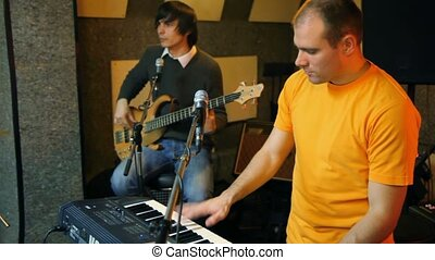 keyboard player and guitarist playing in studio