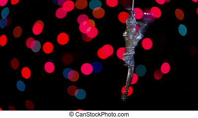 Keychain ballerina swinging on a chain on the background of beautiful bokeh.