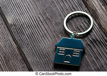 keychain in the shape of a house on wooden boards close-up