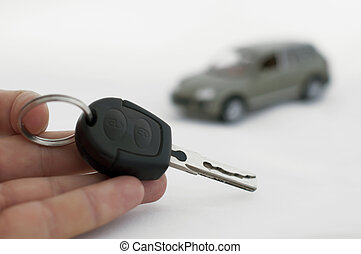 Keys and a car in the background