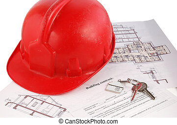 Keys and helmet on building contract and blueprints