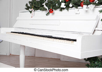 Keys on white upright piano with christmas decor with red balls