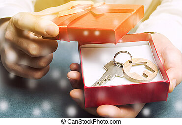 Keys with a house with a gift box and snow. Great offers for real estate in the winter season. Discounts and sale of housing. New Year promotions