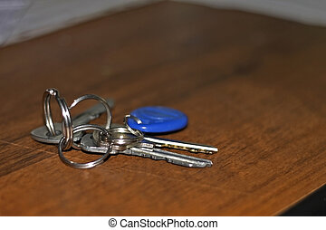 Keys with a rings lay on the brown wood table