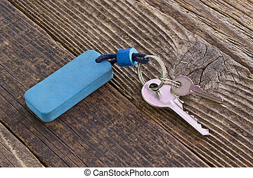Keys with blue tag on wooden background