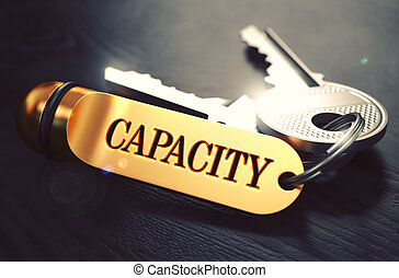 Keys with Word Capacity on Golden Label over Black Wooden Background. Closeup View, Selective Focus, 3D Render. Toned Image.