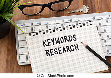 Keywords research words on notebook with computer keyboard