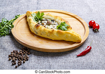 Khachapuri-boat with meat and mushrooms. Ingredients: beef tenderloin, mushrooms, cream sauce, herbs. Khachapuri is served on a round light wooden Board.