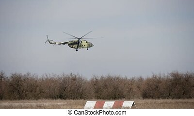 Khaki rotorcraft with rotating blades flying in a rusty...