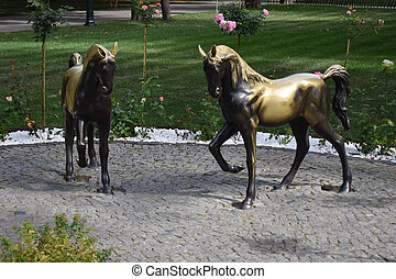 Kharkiv, Ukraine, september 6, 2020: Horse Sculpture in Gorky Park. Two metal sculptures in the park in autumn against the background of flower beds and green grass.
