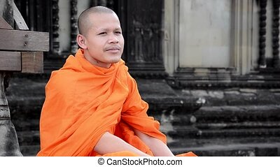 khmer monk smoking a cigarette - cambodian monk in angkor...