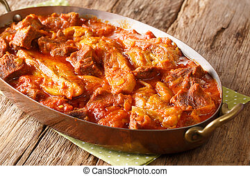 Khoresh Bademjan Slowly stewed lamb meat with eggplant, spices close-up in a pan. Horizontal