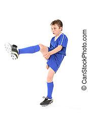 Kick - A boy dressed in soccer uniform kicking. Focus to...