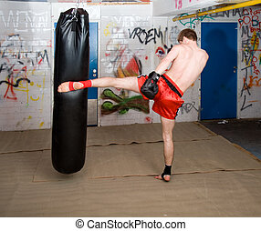 Kick - A muay thai fighter kicking a boxing bag in a...