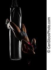 girl hanging on a boxing bag