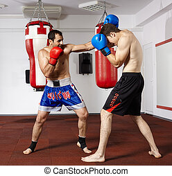 Kickbox fighters sparring in the gym - Two young kickbox...
