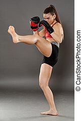 Kickbox girl delivering a kick
