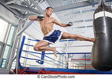 Kickboxer. Confident young kickboxer training at the...