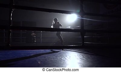 Kickboxer girl in the ring punches her hands and feet ....