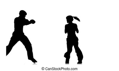 Kickboxer girl kicks on the head of an opponent. Silhouette. White background. Slow motion