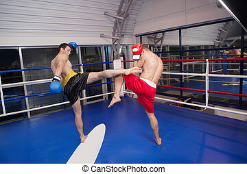 Kickboxing. Two confident men kickboxing on the ring