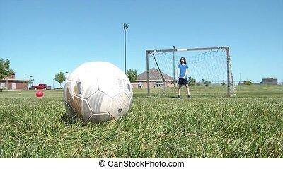 Kicking Soccer Goals at Goalie - Girl stands in goal in...
