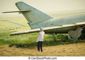 kicsi lány, alatt, egy, baseball sapka, -ban, a, repülőtér, közel, a, öreg, hadi, aircraft.