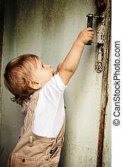 Kid and door - Year-old child pulls the door handle and...