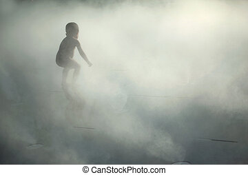 Kid playing in mist and water steam