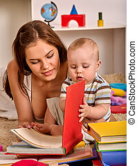 Kid and mother baby boy lying on floor and read book. -...