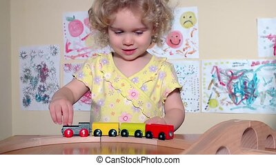 Kid and mother playing together with wooden train at...